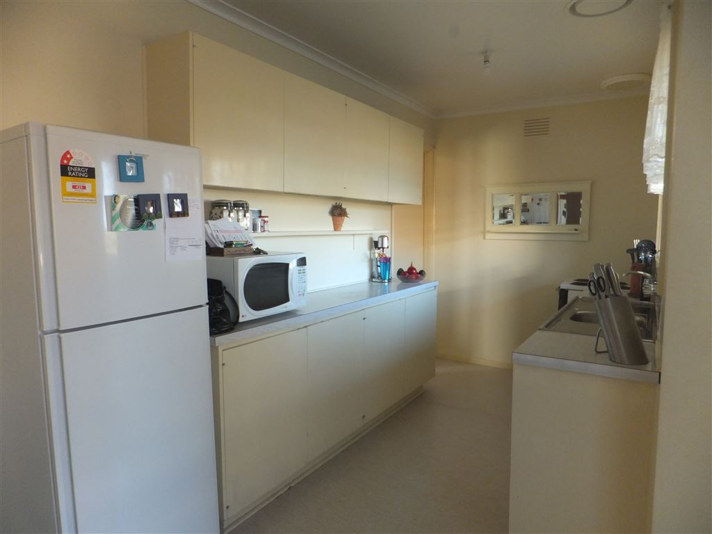 Kitchen with electric stove, ample bench & cupboard space & large window overlooking rear yard