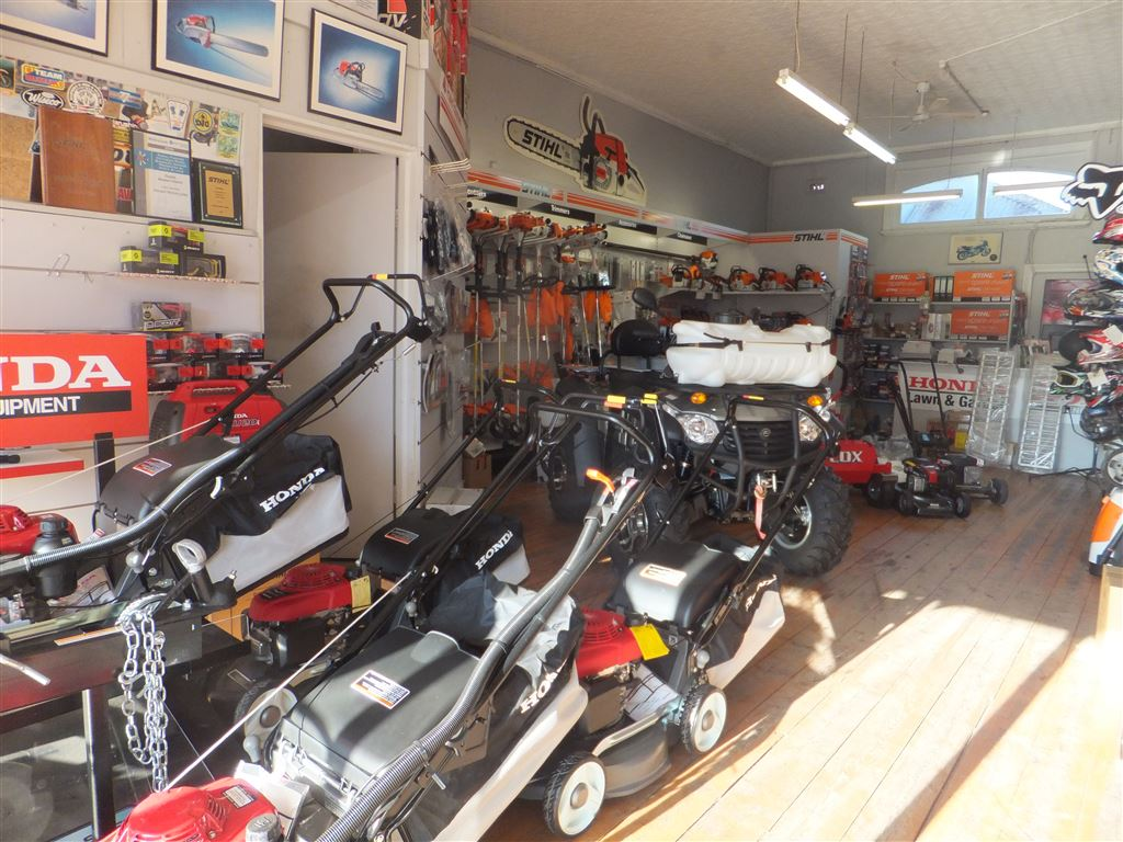 First showroom floor showing motor mowers & Stihl garden equipment, small computer office on left and service counter at rear