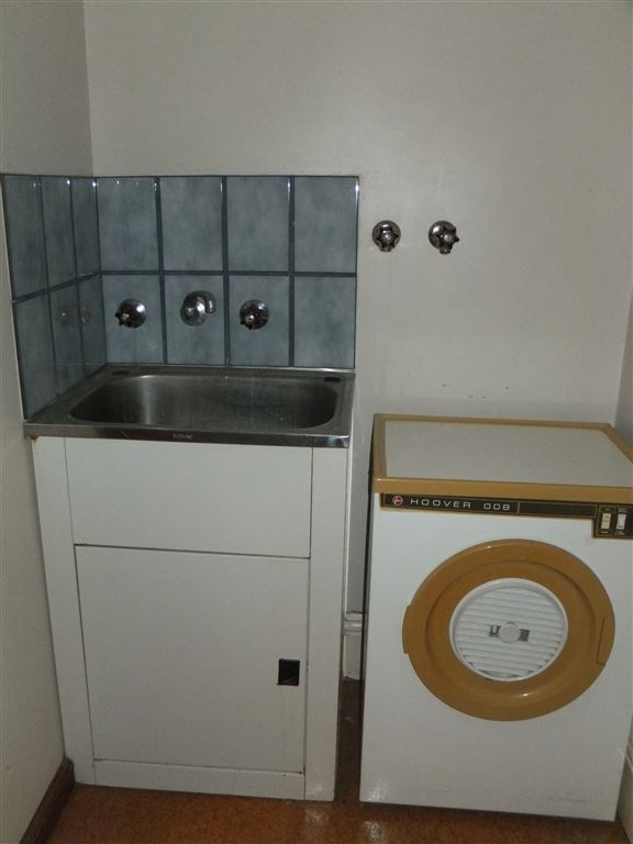 Laundry with trough and tiled splashback