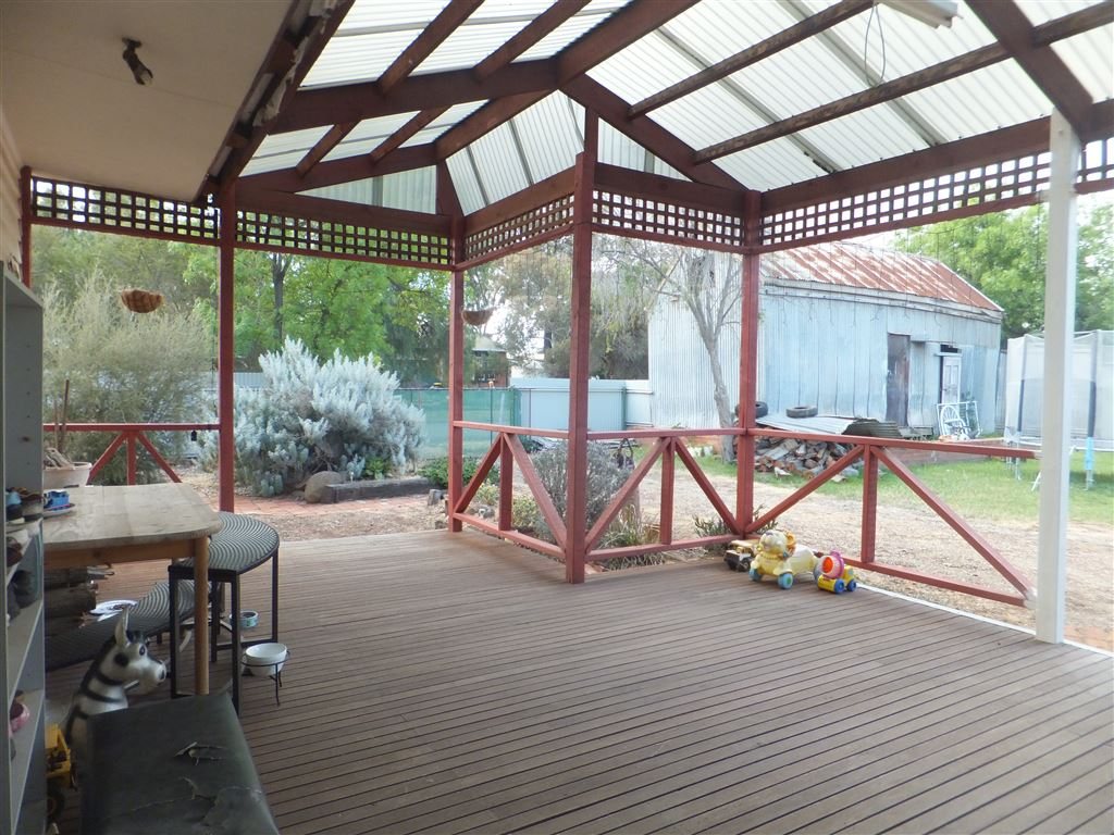 Fully covered decking area overlooking rear yard and workshop/storage shed