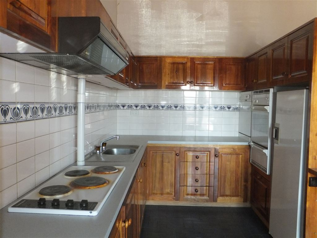 Country style kitchen with in-bench hotplates, rangehood, wall oven, fridge recess and fully tiled splashback