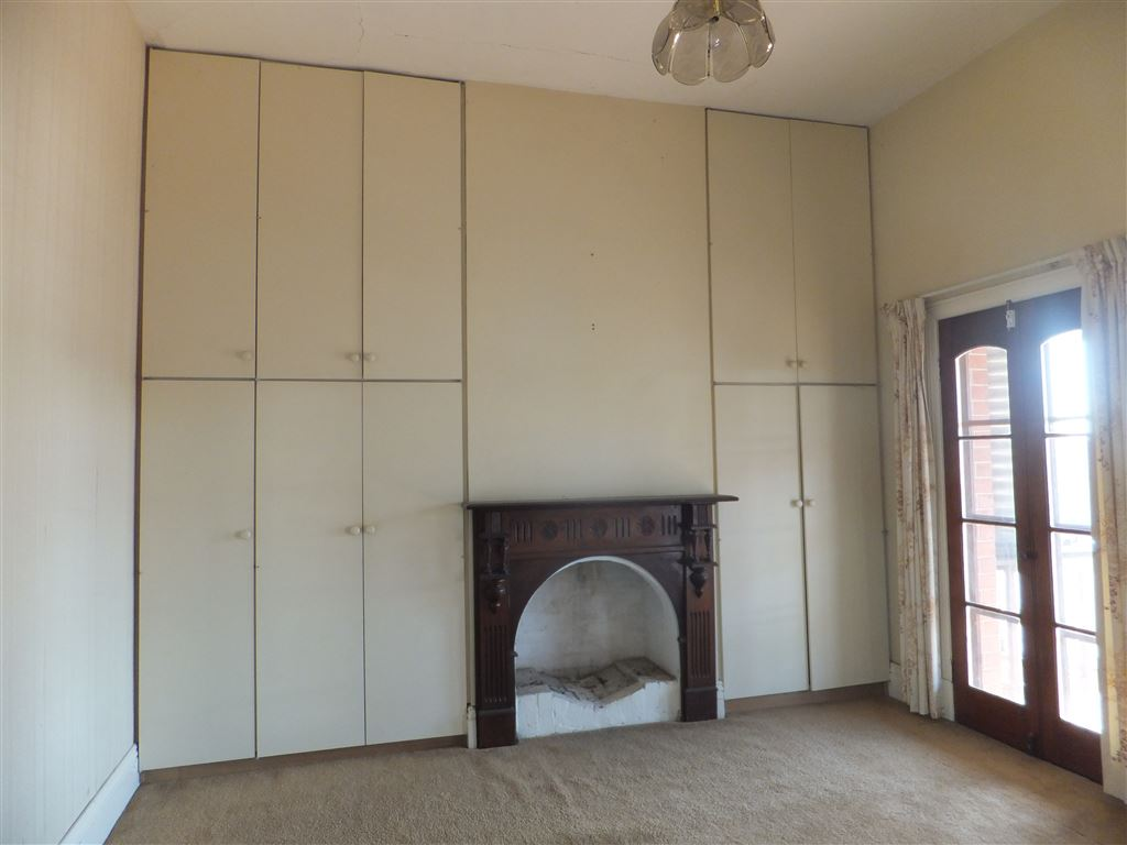 Second bedroom which overlooks balcony. Bedroom has floor to ceiling built-in wardrobes and original firepolace