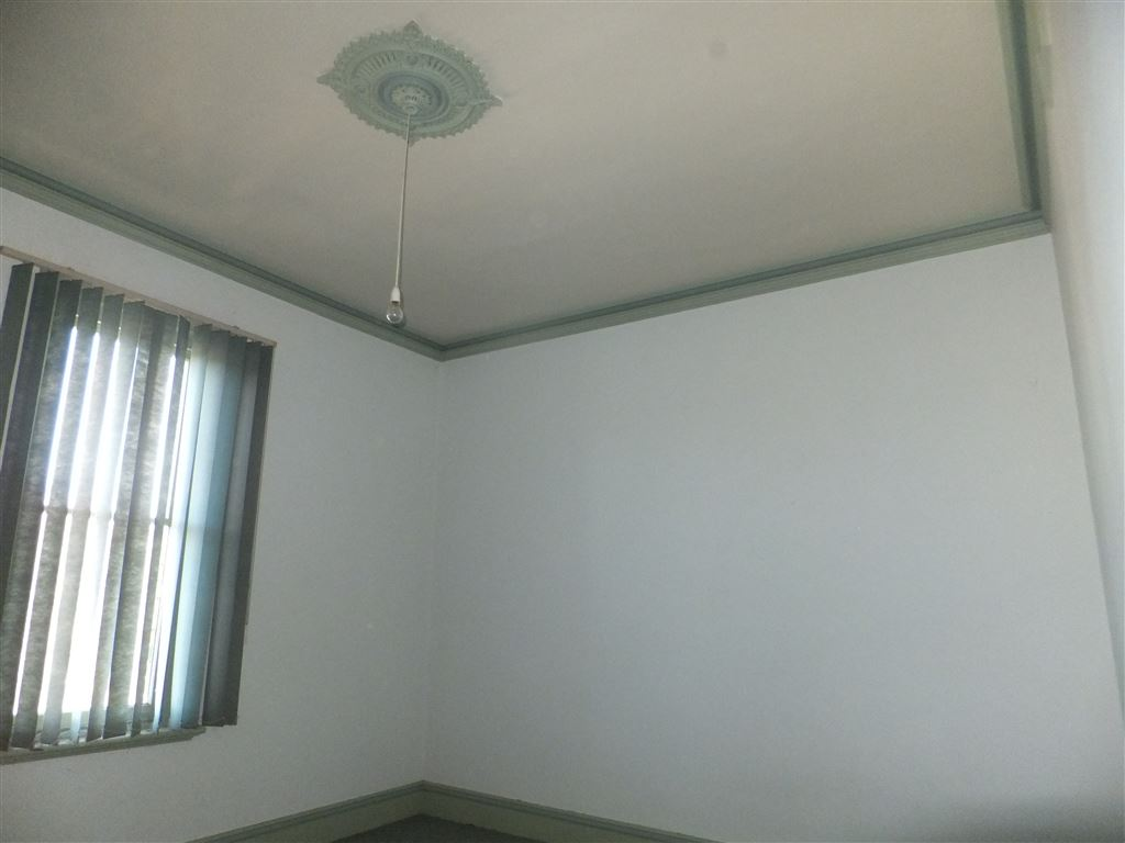 Main bedroom with pressed metal ceilings, decorative ceiling rose and window looking down across to rear of block