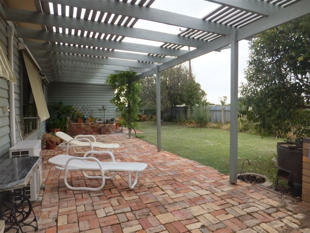 Brick paved pergola along front of home