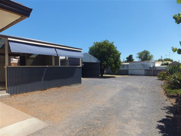 Looking from driveway down back yard towards carport, workshop and clothesline; patio on left