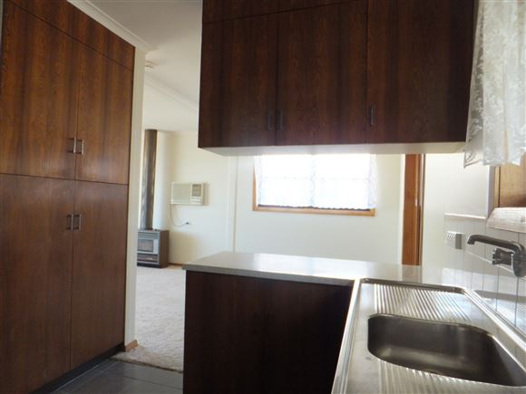 Kitchen through to dining area, large pantry on left & storage cupboards above bench
