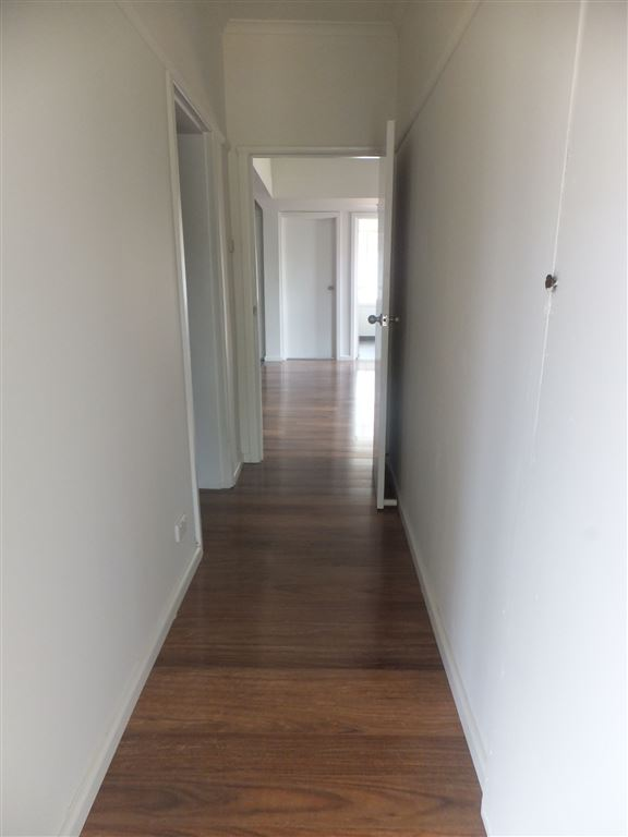 Central hallway from front entrance leading down to living area and open plan kitchen/dining area