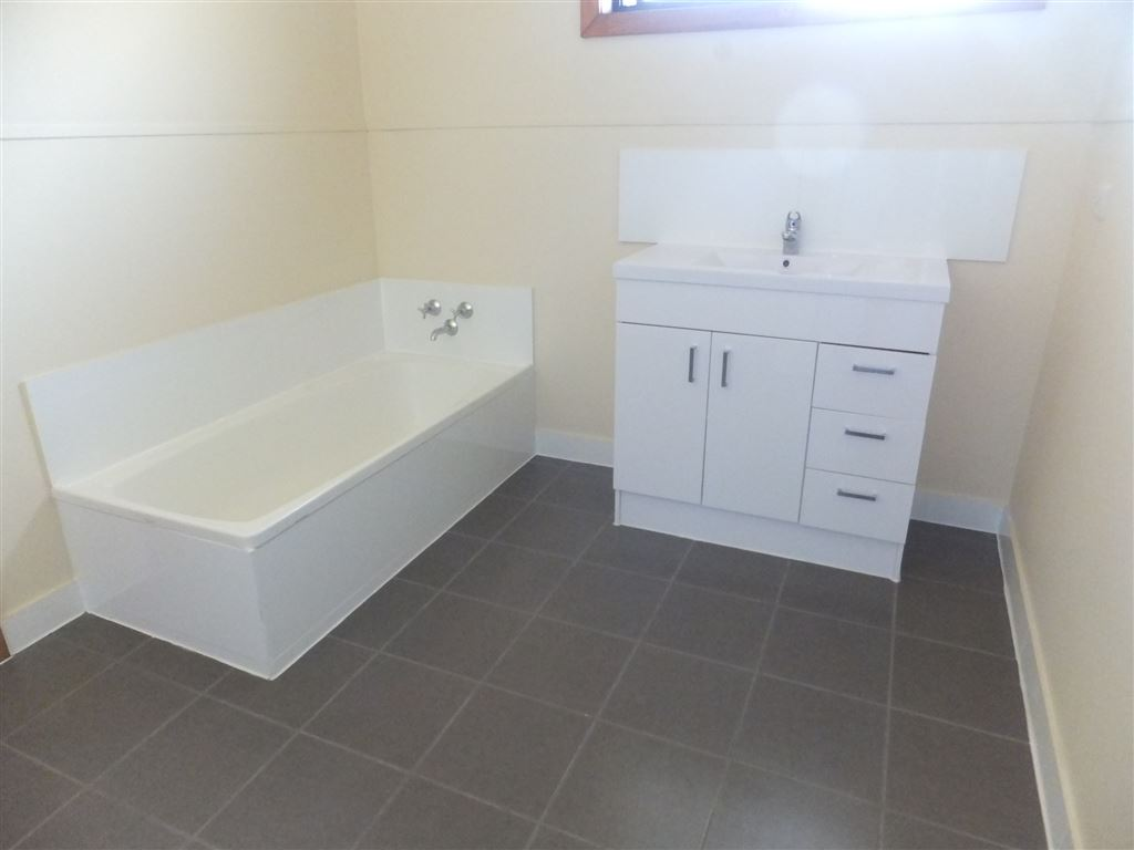 Newly renovated bathroom with full sized bath, modern vanity, new shower & new tiled floor