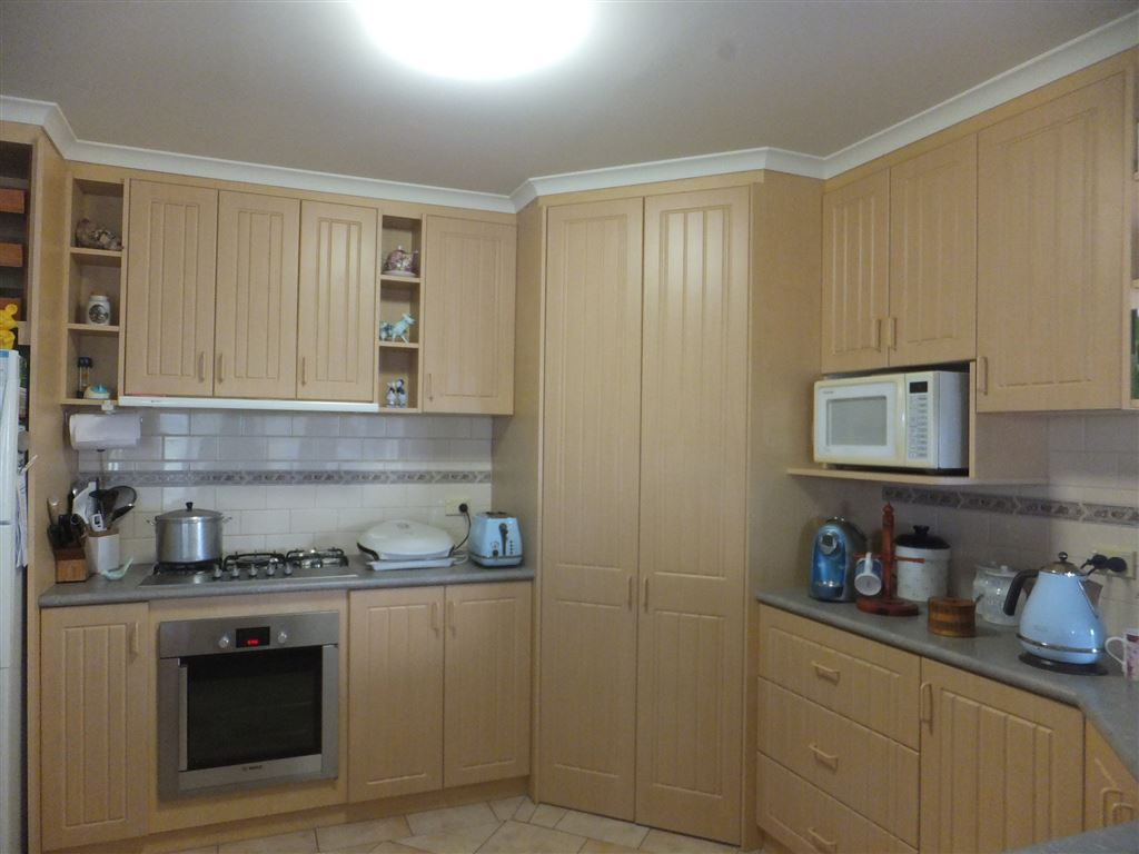 Kitchen view to large pantry, microwave & fridge niches & loads of bench space