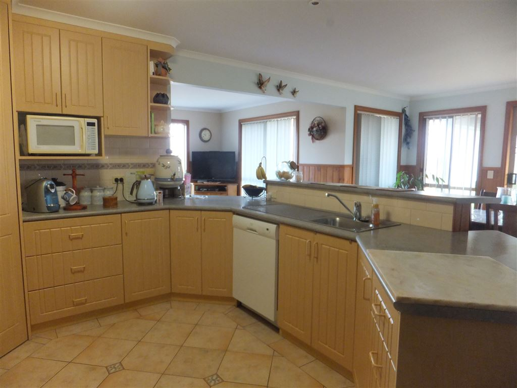 Kitchen view showing ample cupboard space, dishwasher & view to lounge & dining rooms
