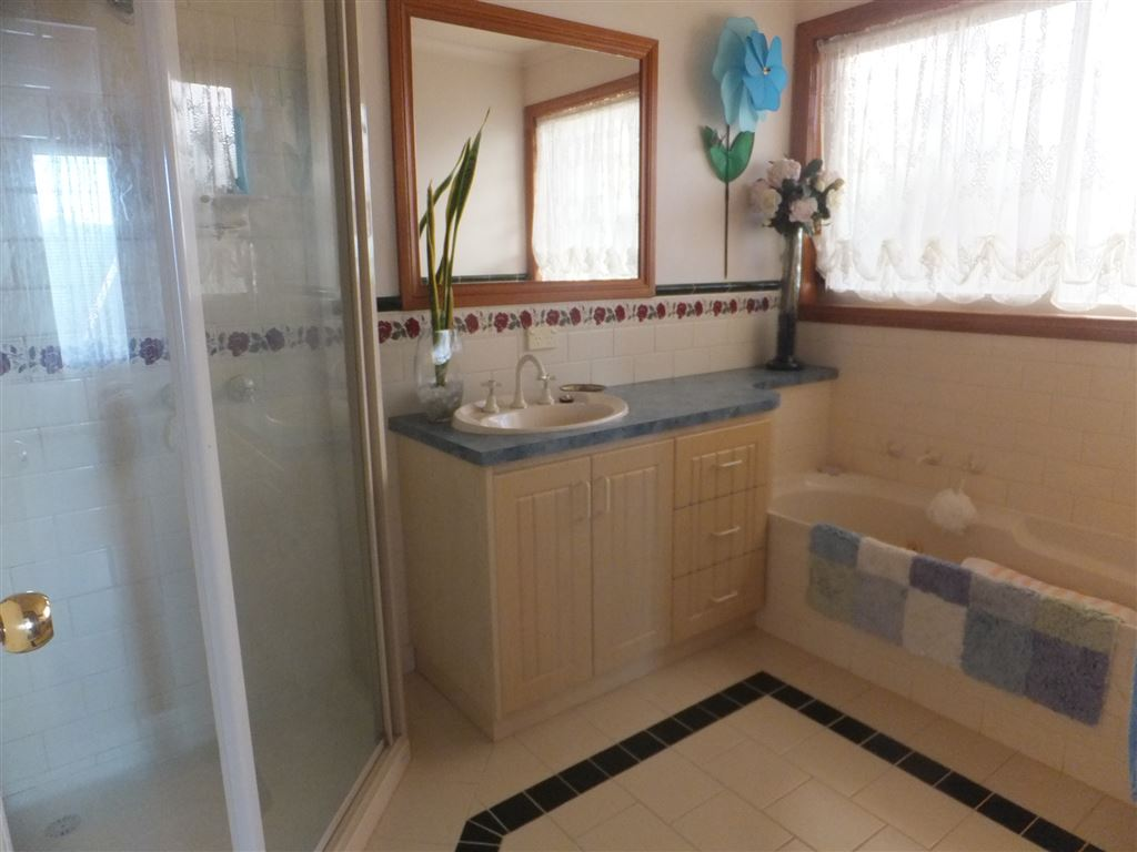 Main bathroom with shower, bath, vanity & feature tiling