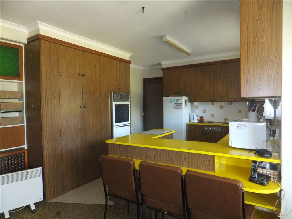 Looking from dining room to kitchen, breakfast bar(door at rear of kitchen is formal lounge). Kitchen has St George oven & in-bench electric hotplates