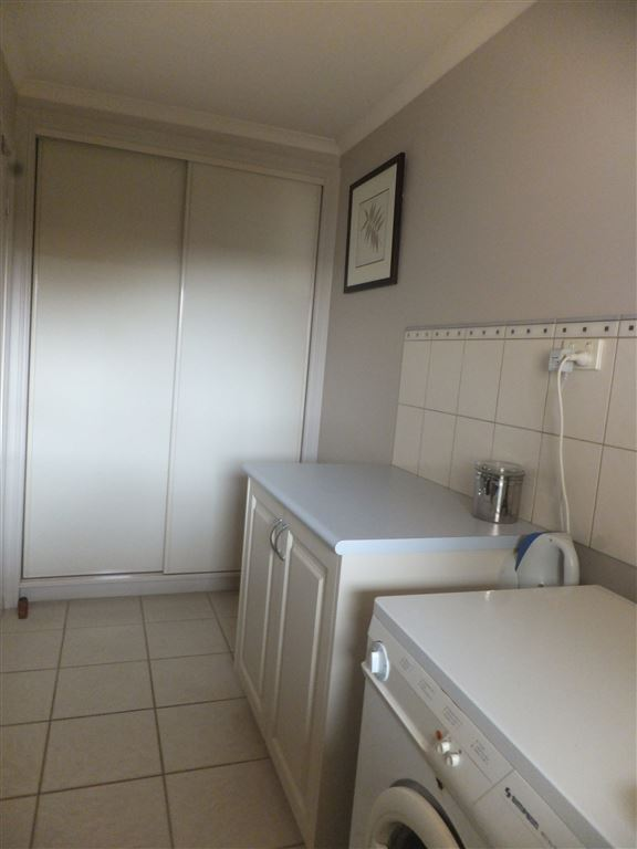 Huge fully tiled laundry with wall of storage cupboards