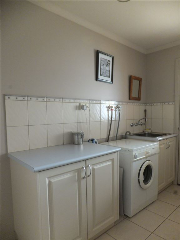 Second view of laundry with fully tiled splash back and bench space