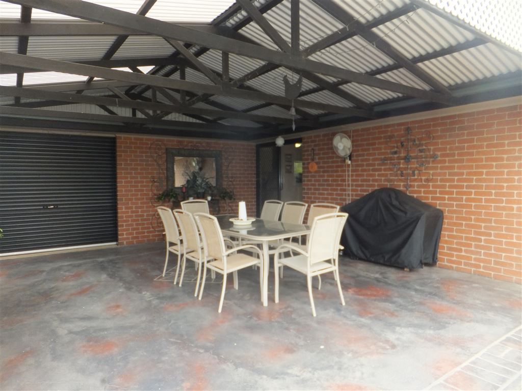 View two of outdoor entertaining & dining area looking toward kitchen access sliding doors. Roller door on left of photo leads to double garage and also provides access for all vehicles to access rear sheds & workshops