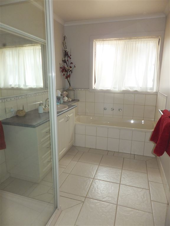 Main bathroom with full tiling in very tasteful tones, full sized bath and separate shower