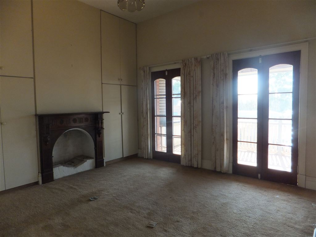 Main bedroom with large built-in wardrobes, original fireplace and two sets of french door s leading out onto balcony
