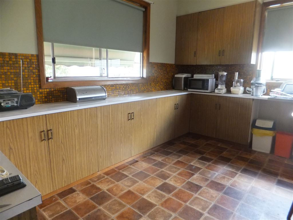 Spacious kitchen with lots of bench space & windows running along two sides. Breakfast bar on left of photo opens through into main lounge