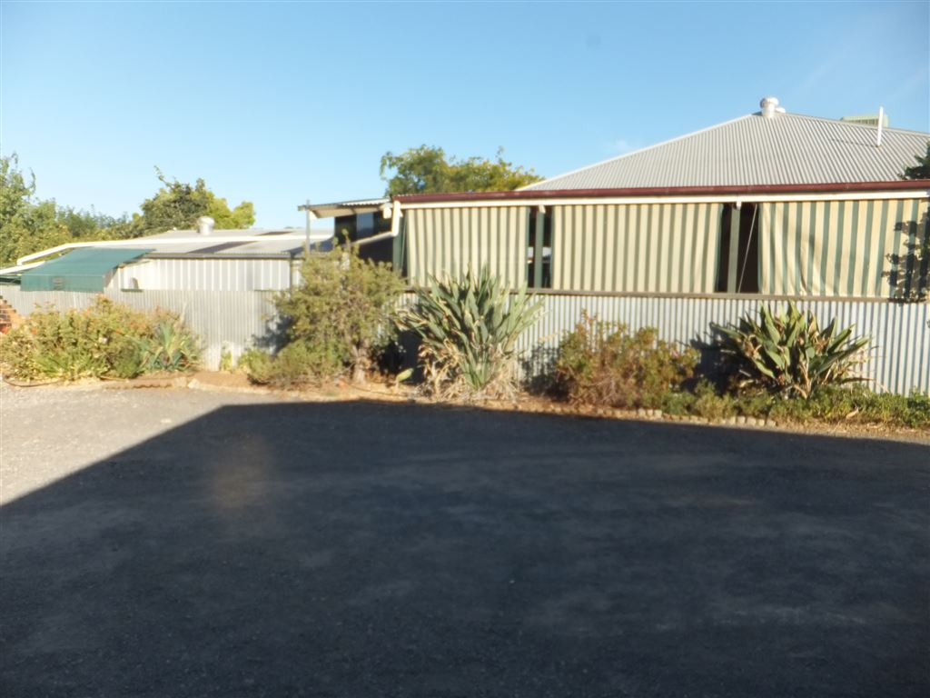 Yard laid with easy care blue metal and garden beds with drought tolerant plants