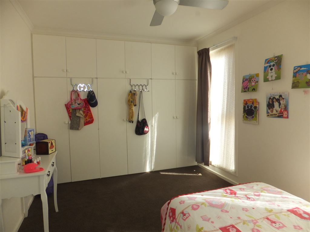 Bedroom Three with full wall of built-in wardrobes, ducted heating & cooling & ceiling fan
