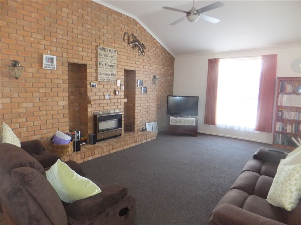 Main lounge with feature brick wall, vaulted ceilings and gas heater(additional to ducted heating if required).