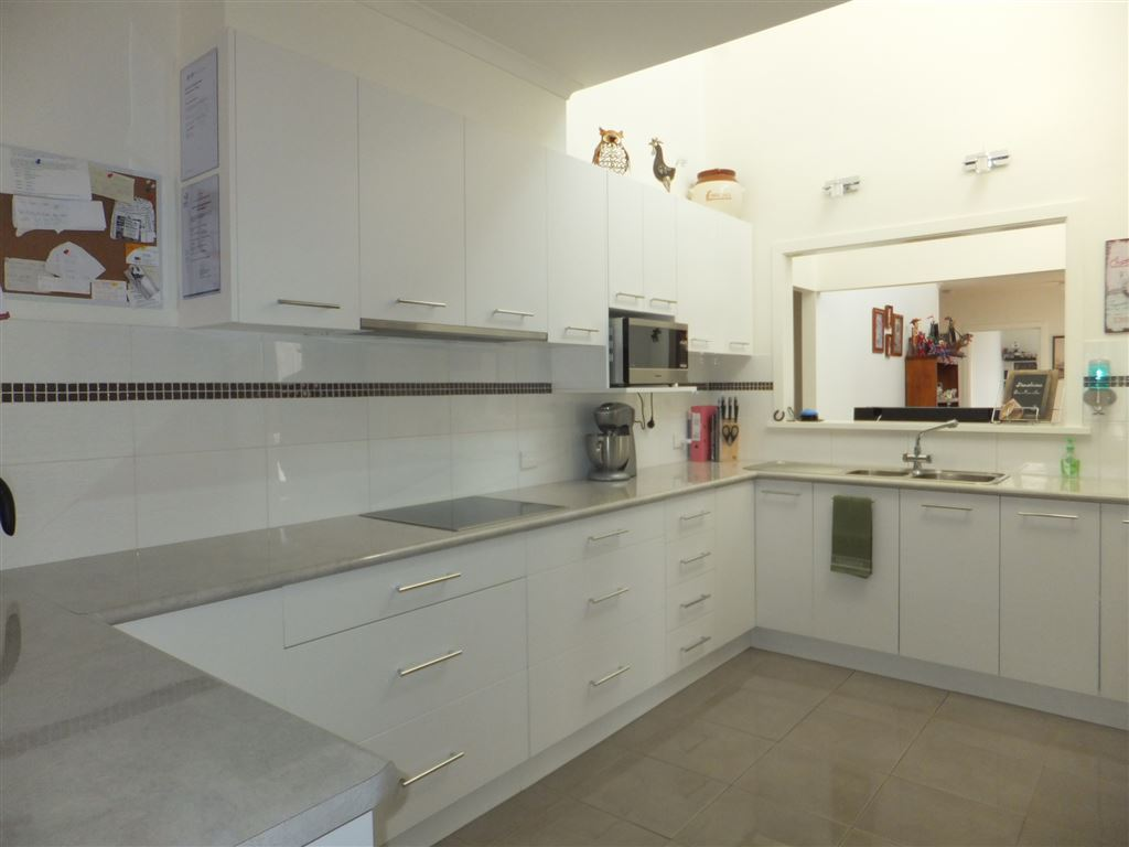 Kitchen with very clean lines, in-bench ceramic hotplates & roll out range hood, lots of storage drawers & quality tiled splashback