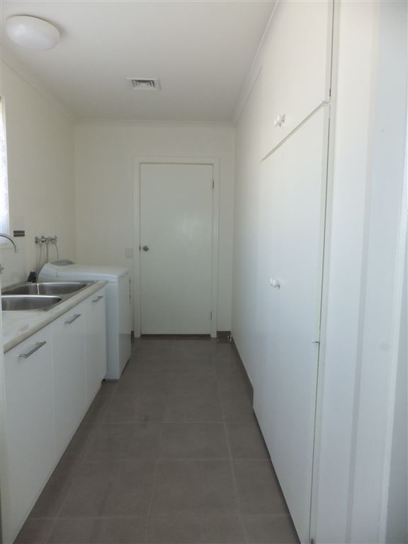 laundry showing full wall of built-in storage cupboards