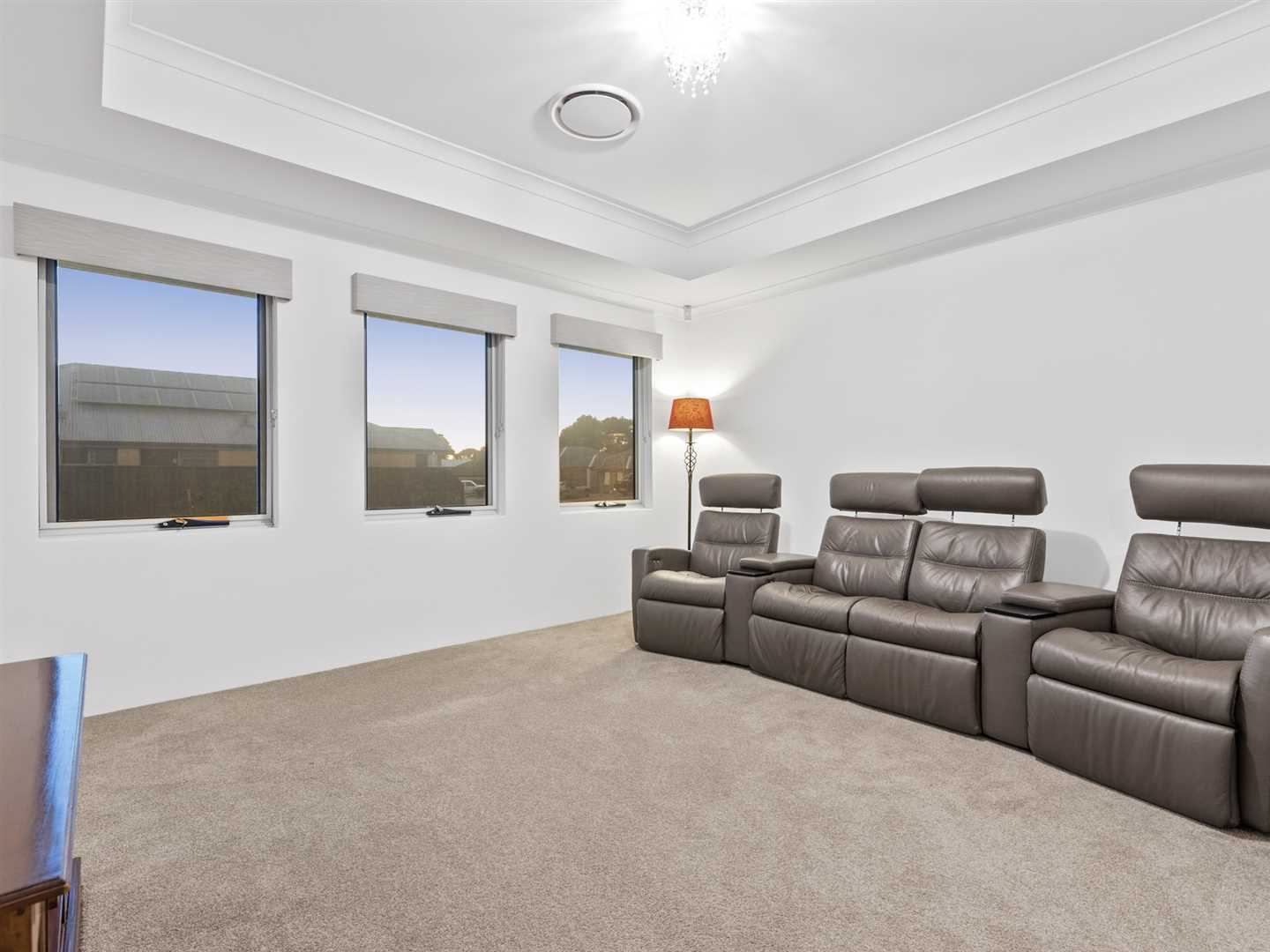 Dedicated theatre room with tinted windows and coifered ceiling