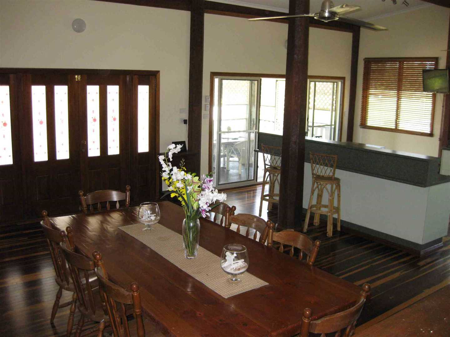 Inside view of part of home showing part of dining area with part of kitchen in the background
