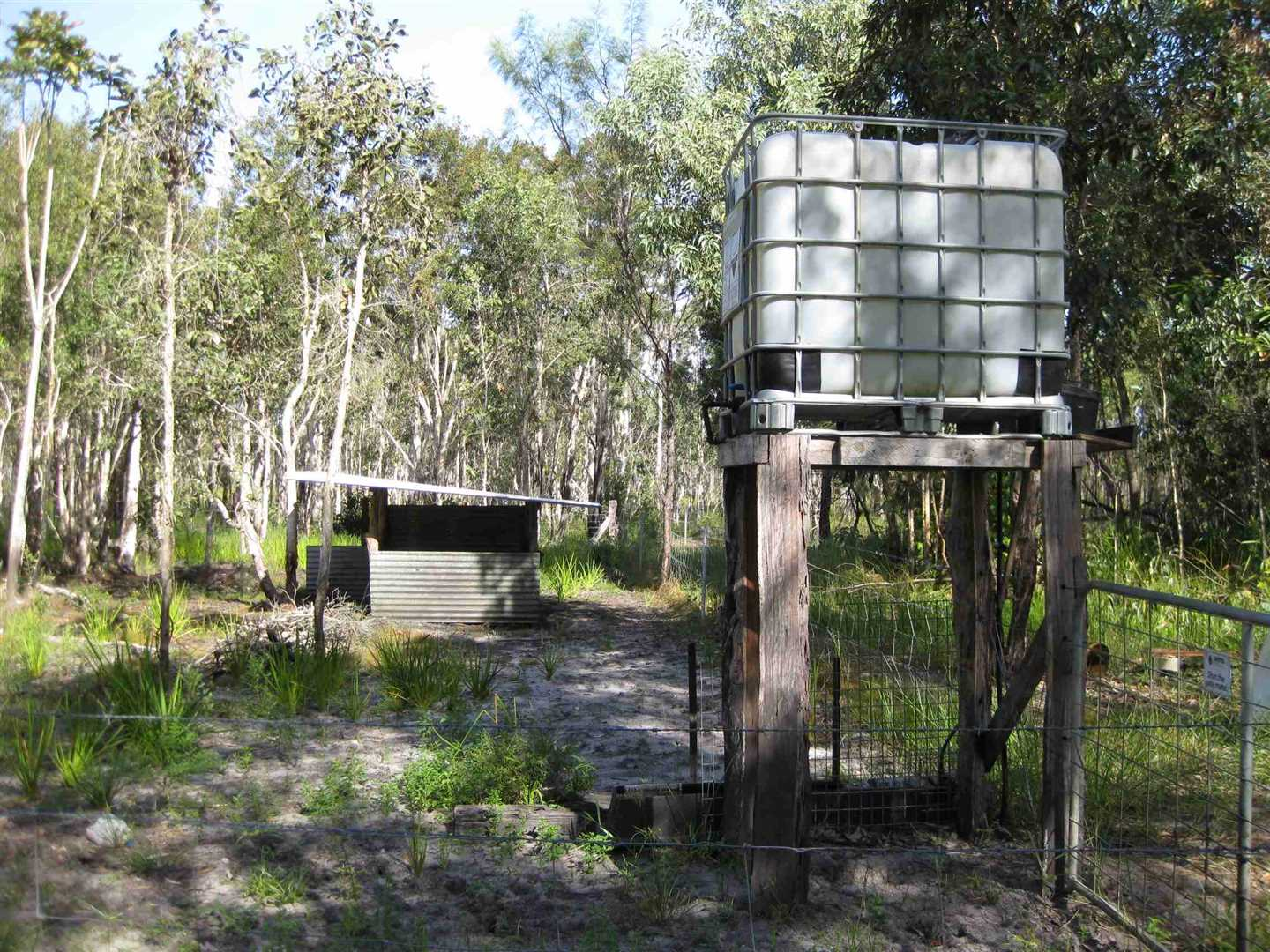 View of part of property showing part of 1,000 litre tank on stand (for livestock water use) and bush livestock shelter