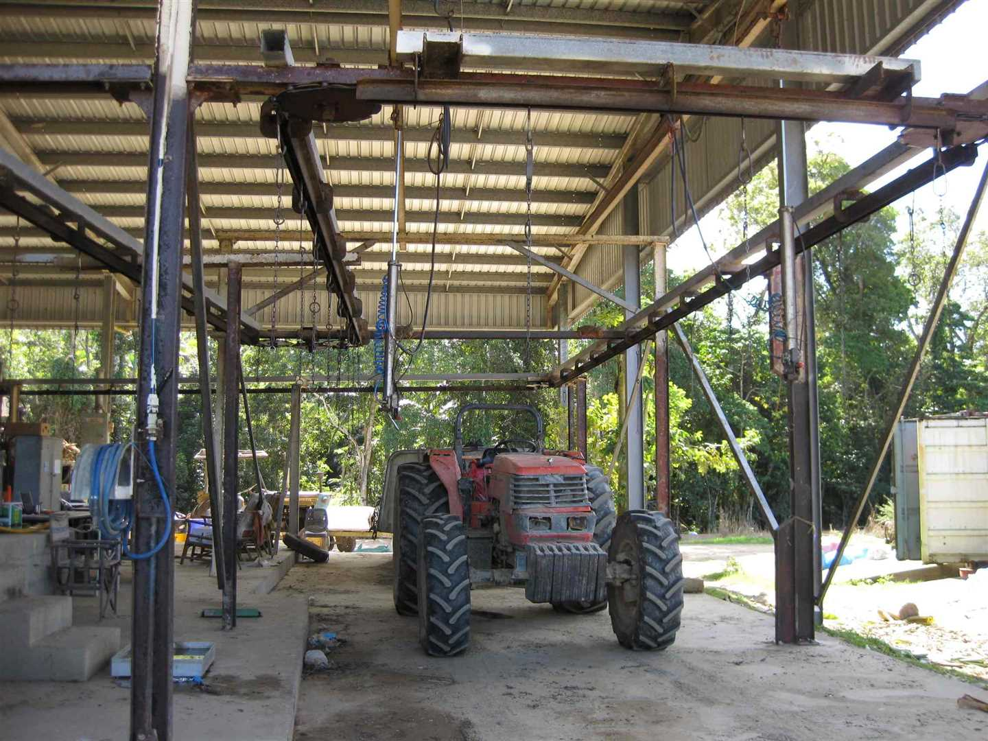View of part of inside packing shed showing part of banana bunch line with two banana bunch lifting rams