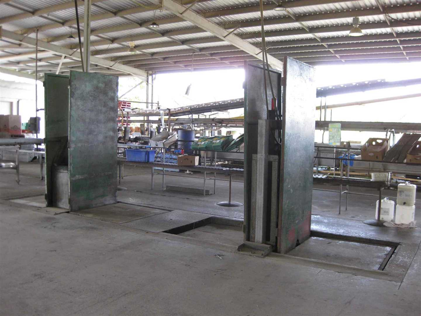 View of part of inside packing shed showing part of two double hydraulic pallet stackers