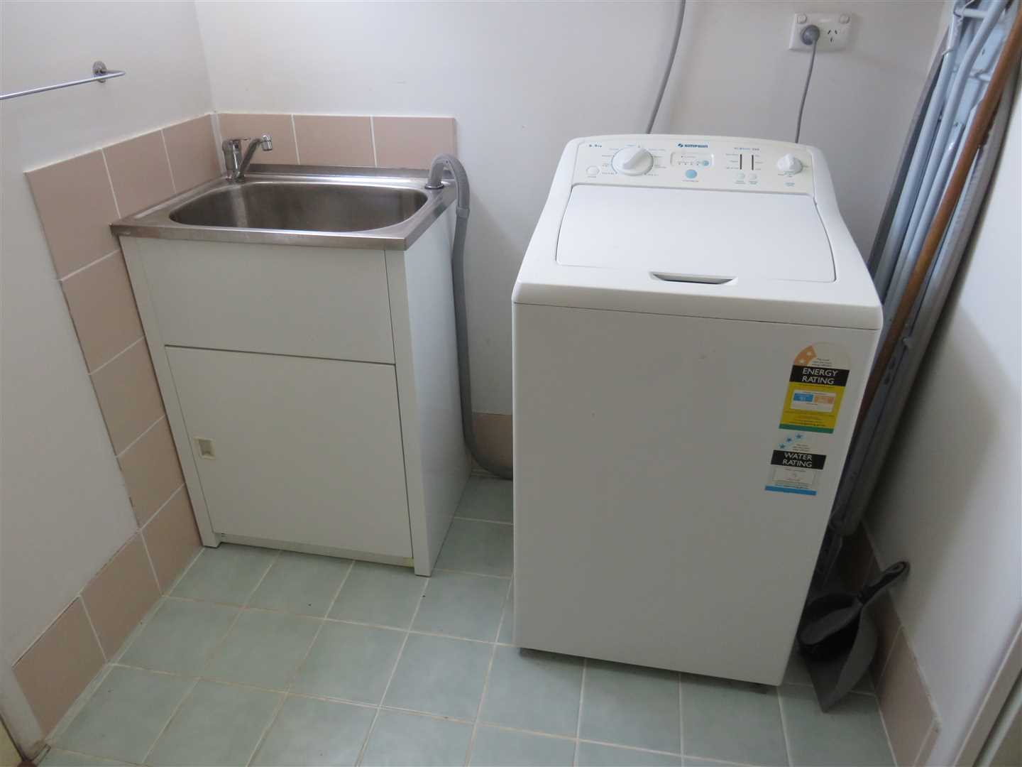 laundry with washing machine in shed unit