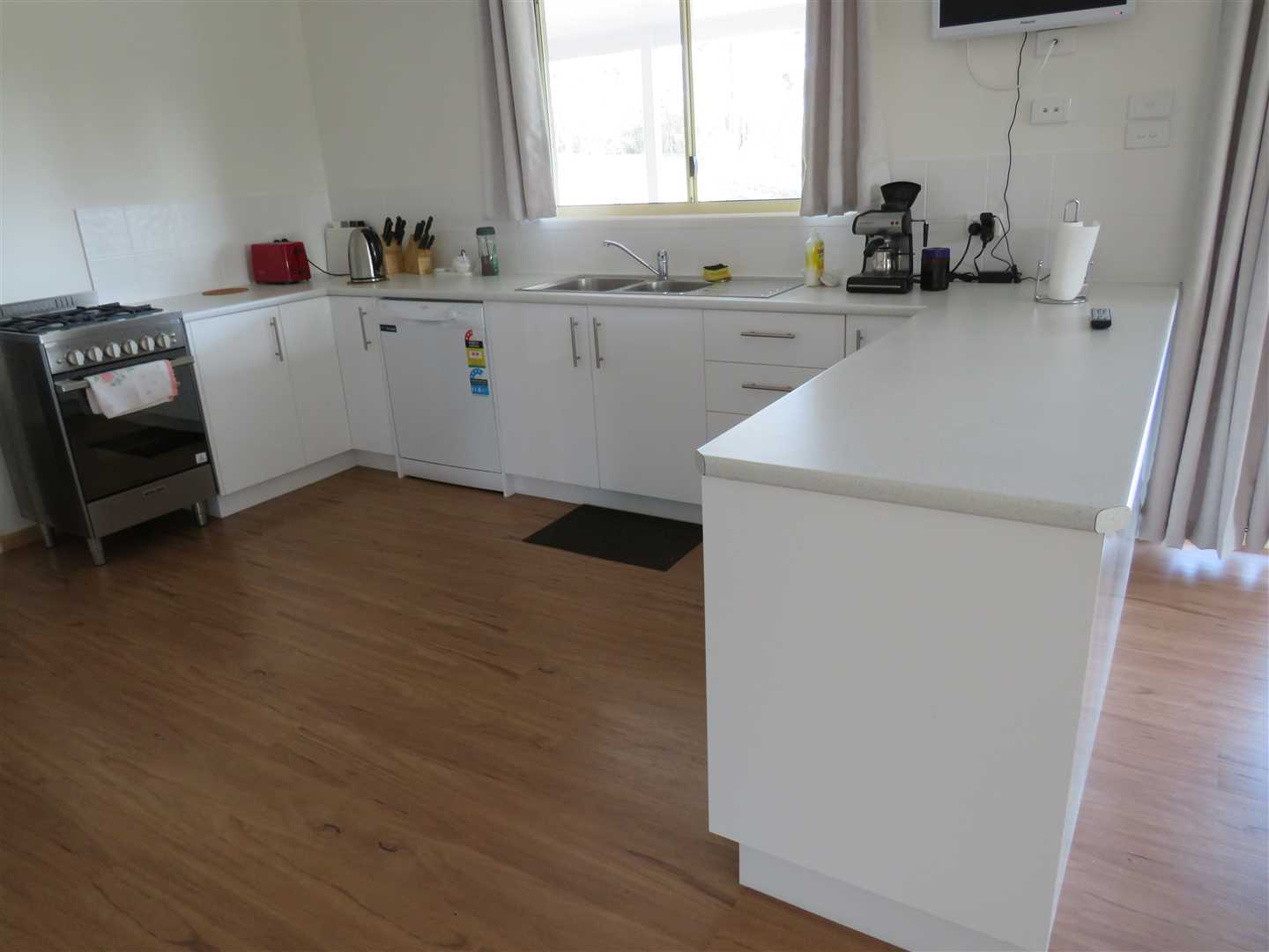 modern kitchen,under sink scraps,corner fold out shelves,dishwasher,double sink with flick mixer,lino floor covering