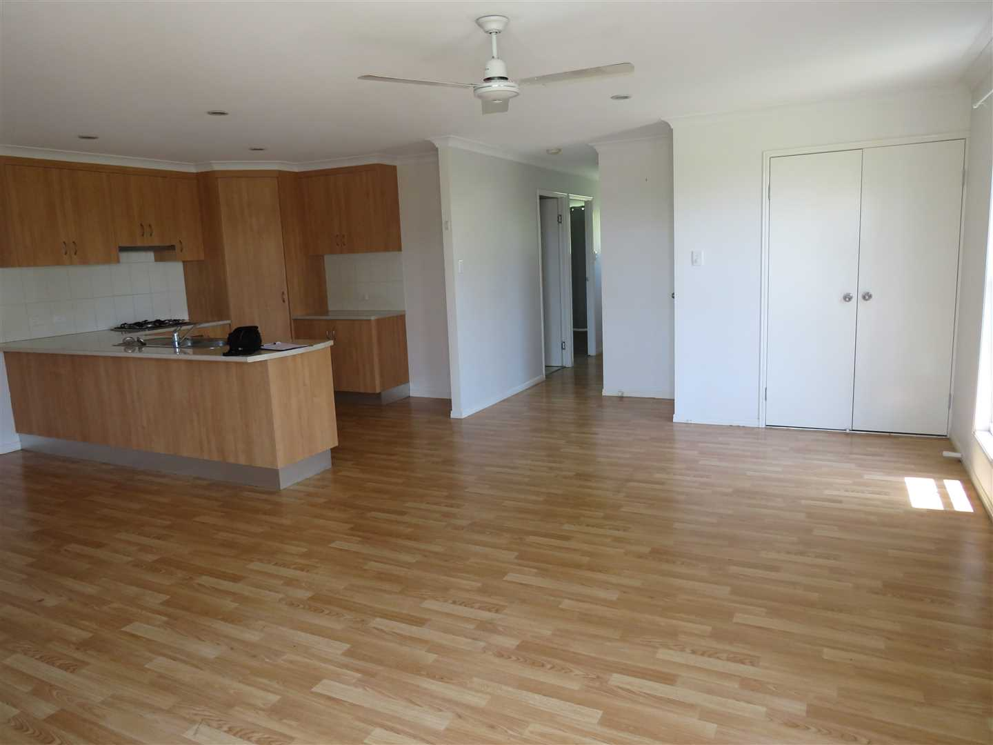 hallway leads to 2 rooms and main bathroom. Laundry behind double doors.Ceiling fans, droplights. Vinyl floorcoverings