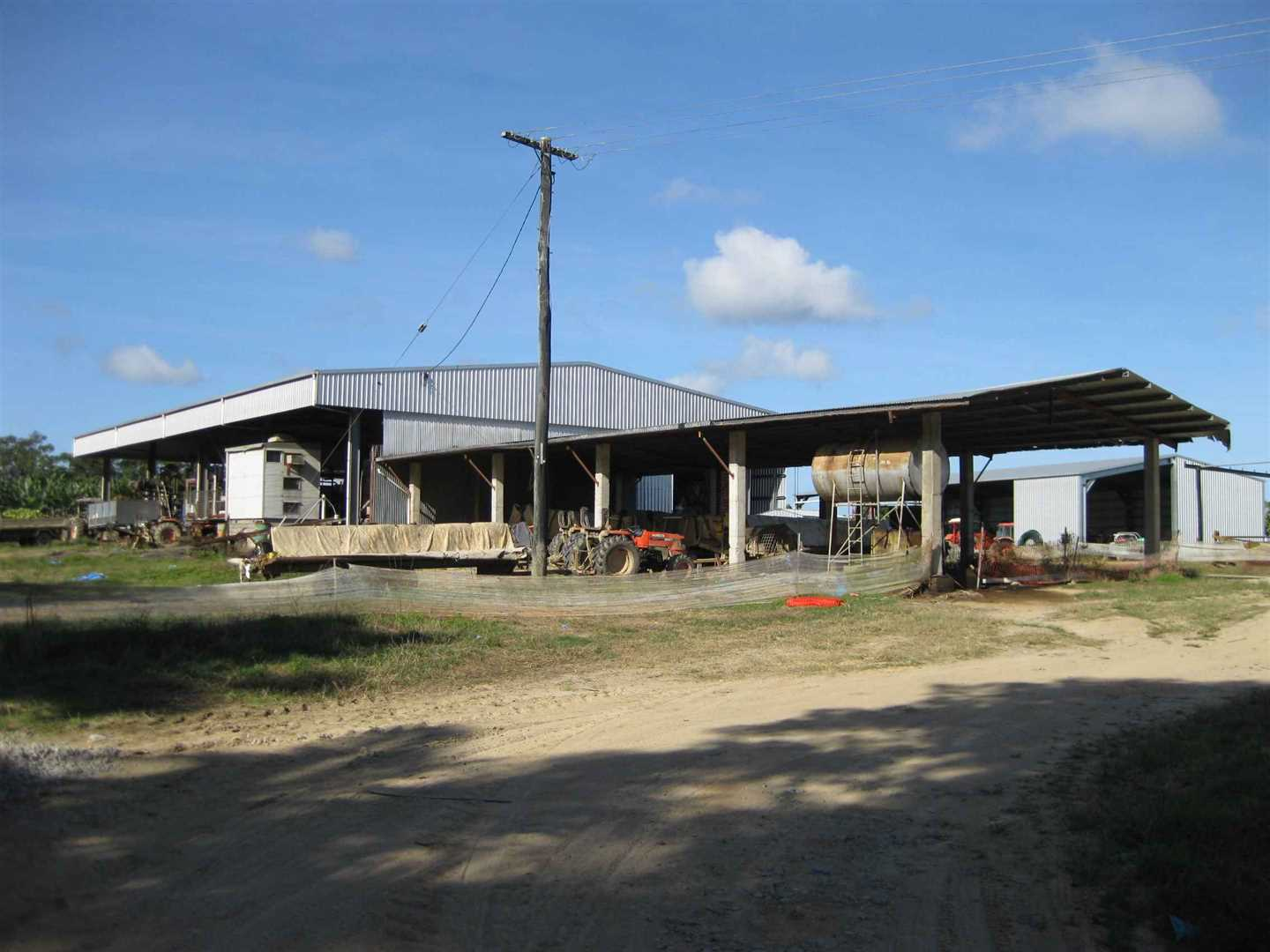 Outside view of part of packing shed, photo 3 with 4 bay machinery shed in front