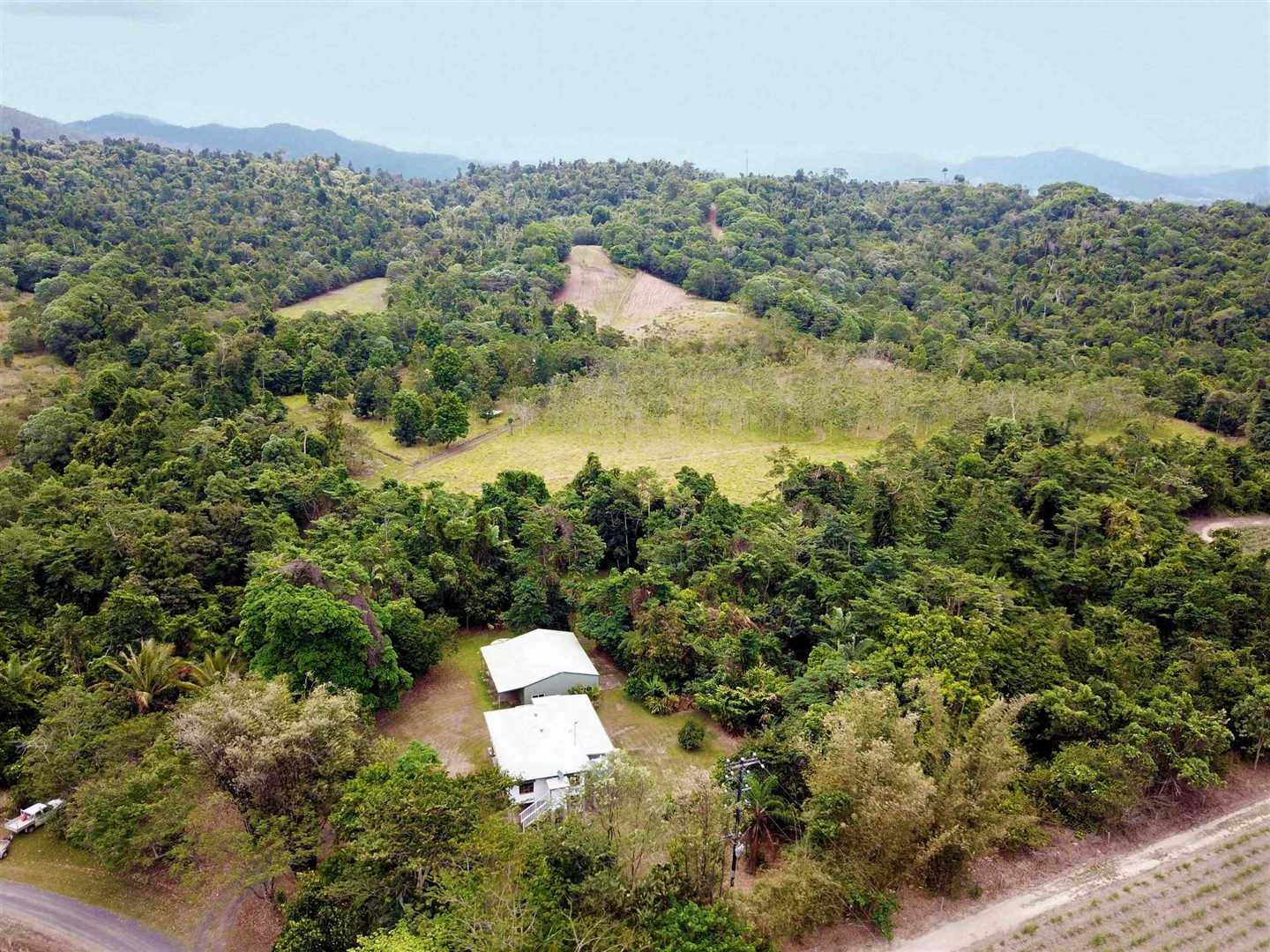 Aerial photo showing part of the property entrance, home, shed, part of the fenced paddocks and some of the cleared parts of the property