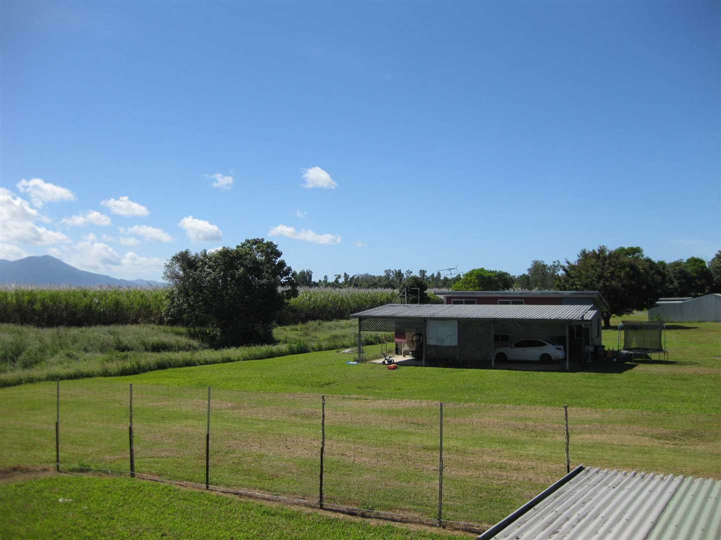 View from part of high-set home back verandah showing part of property and separate split level home. Fence shown excluded, property of the tenant