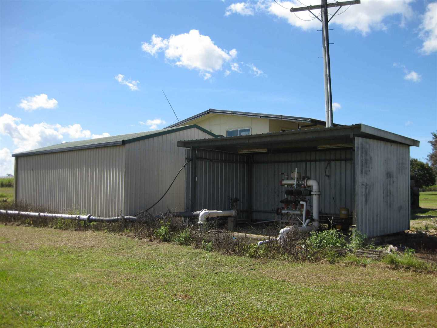 View of part of lockable shed & adjacent pump shed with high-set home behind