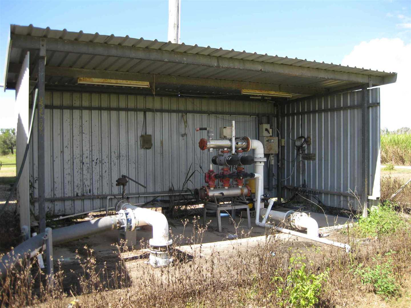 View of part of pump shed adjacent to high-set home. Note that irrigation piping, filters and items shown are not in use or working condition